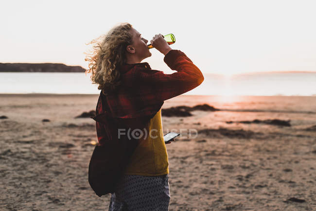 Teenage girl relaxing at the beach, having a drink — Stock Photo