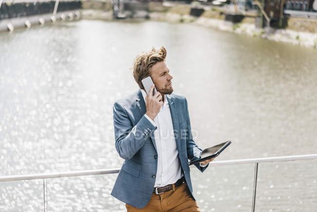 Homme d'affaires avec tablette sur téléphone portable — Photo de stock