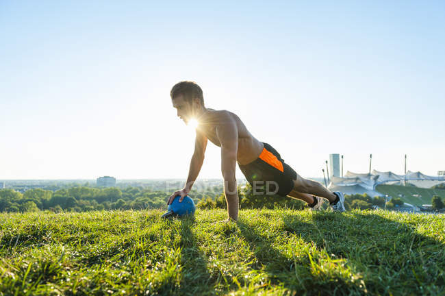 Man exercising with kettlebell on meadow in park — Stock Photo