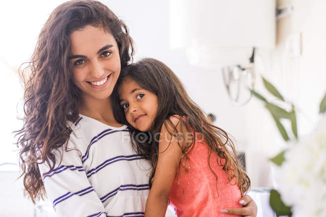 Portrait of smiling teenage girl and her little sister — Stock Photo