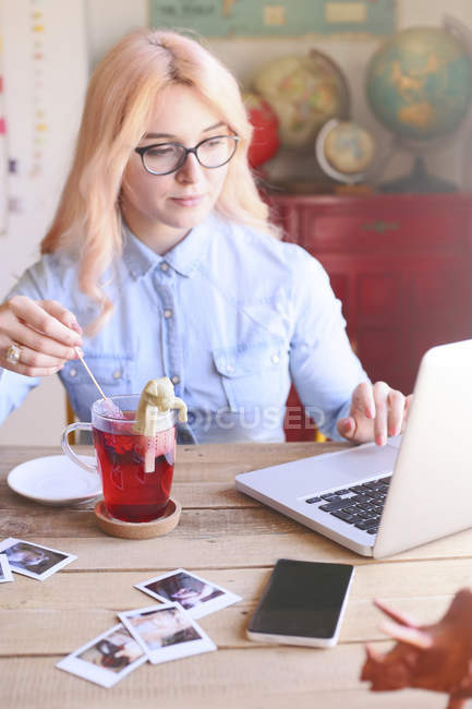 Woman working at home on laptop stirring tea with a sugar stick — Stock Photo
