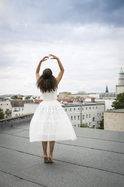 Germania, Berlino, vista posteriore del giovane ballerino che si allena su un tetto — Foto stock
