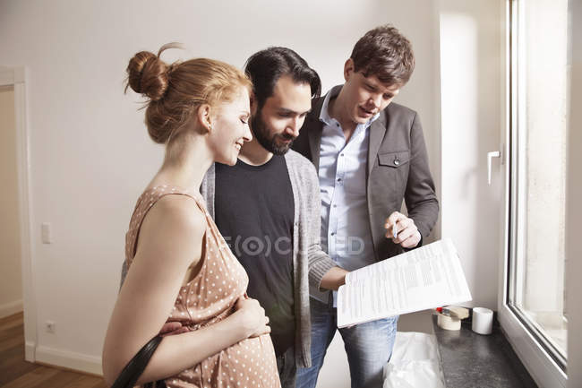 Real estate agent showing expecting parents contract in new apartment — Stock Photo
