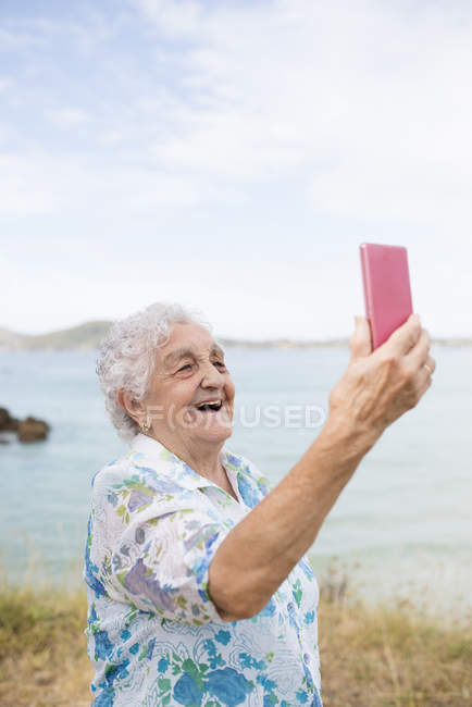 Senior woman taking selfie on beach — Stock Photo