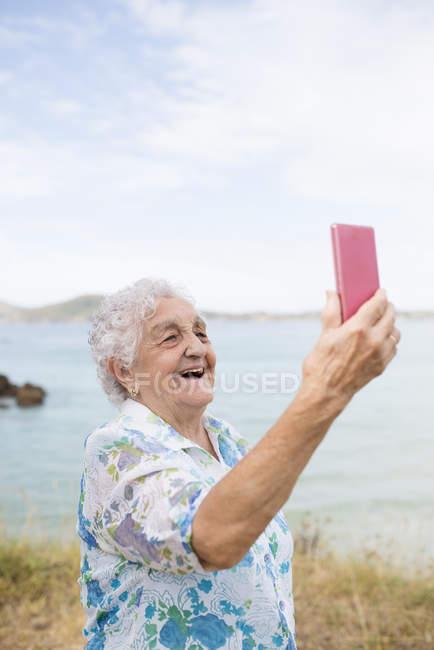 Senior woman taking selfie on beach — Stock Photo
