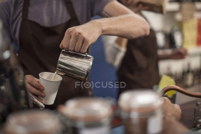Young barista pouring milk into cup — Stock Photo