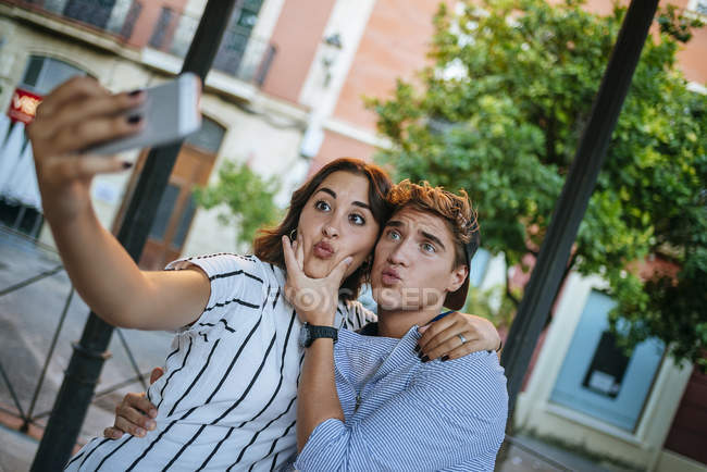 Молодая пара делает селфи со смартфоном — стоковое фото