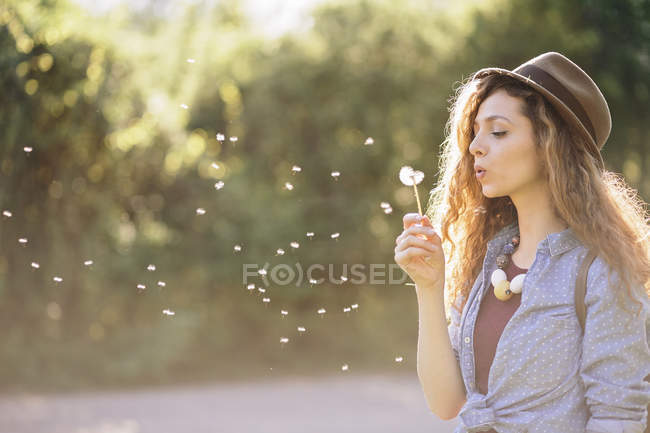 Young woman blowing dandelion — Stock Photo