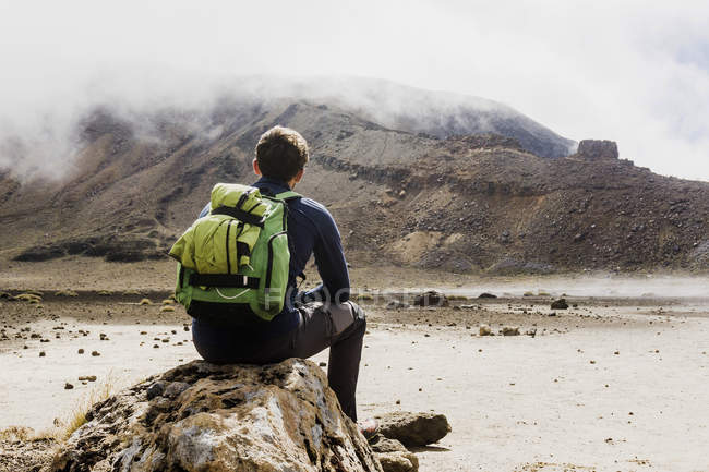 Hiker with backpack sitting on rock — Stock Photo