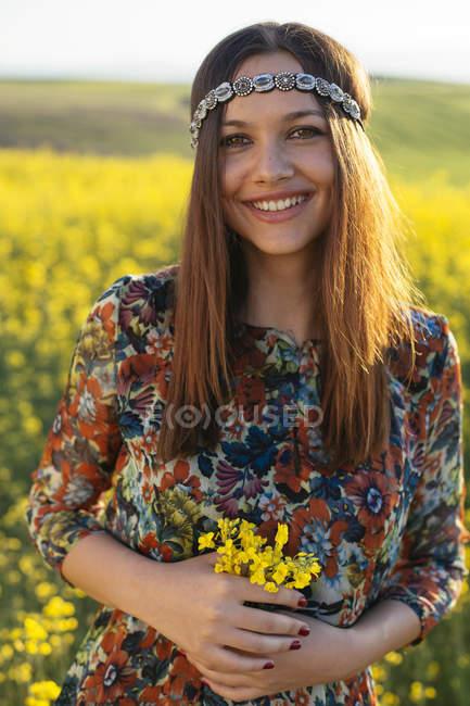 Портрет улыбающегося молодого хиппи, стоящего на рапсовом поле с цветами — стоковое фото