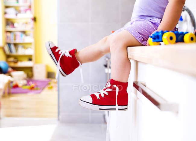 Imagem cortada de menina sentada na cozinha com sapatos de lona de leitura — Fotografia de Stock
