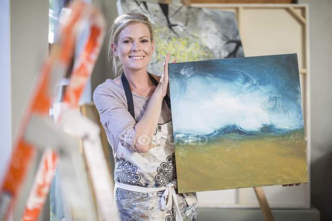 Female painter holding painting — Stock Photo
