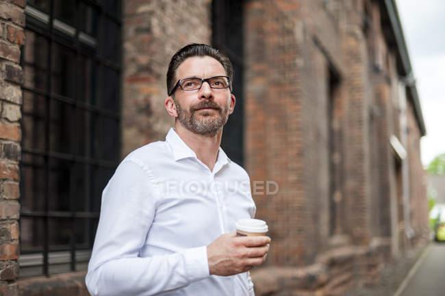 Бизнесмен с кофе идти — стоковое фото