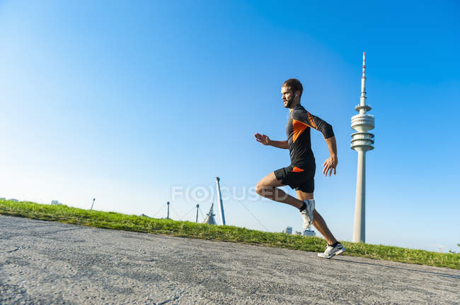 Sportive man running fast on path outdoors — Stock Photo