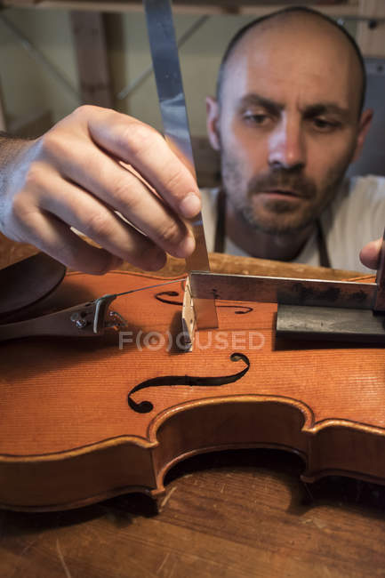 Luthier making measurements during the manufacture of a violin in his workshop — Stock Photo