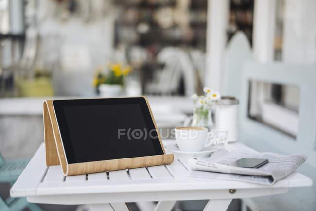 Digitales Tablet, Handy, Zeitung und Kaffeetasse auf dem Tisch im Café — Stockfoto