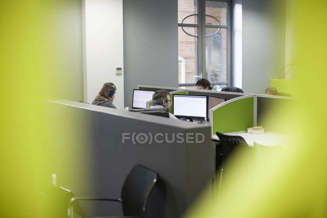 Staff working on computers in office cubicles — Stock Photo