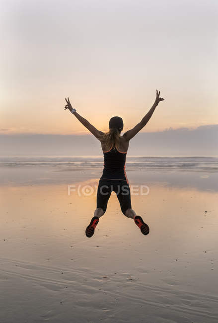 Young athlete woman jumping on the beach at sunset — Stock Photo