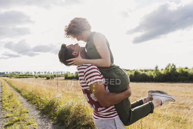 Mann, die Freundin im Feld Pfad anheben — Stockfoto