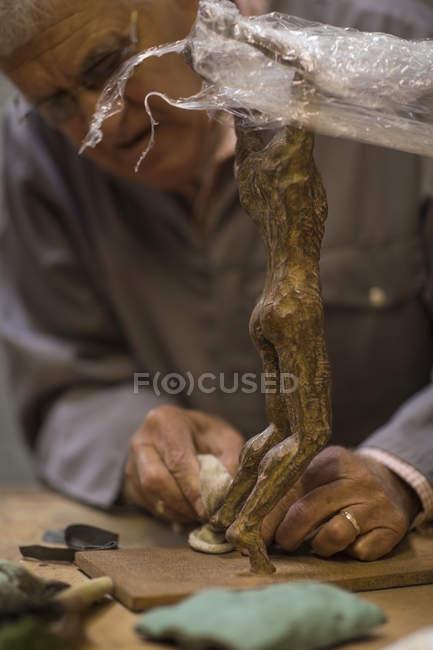 Senior man working on bronze figurine — Stock Photo