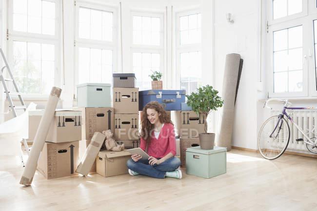 Mujer rodeada de cajas de cartón con tableta digital - foto de stock