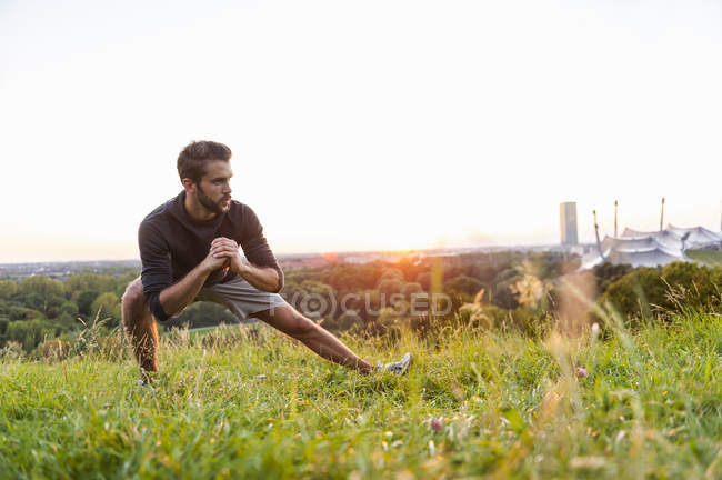 Young athlete stretching on meadow at sunset — Stock Photo