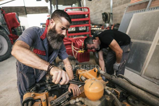 Schwerpunktmechaniker arbeiten in Werkstatt mit Traktoren — Stockfoto