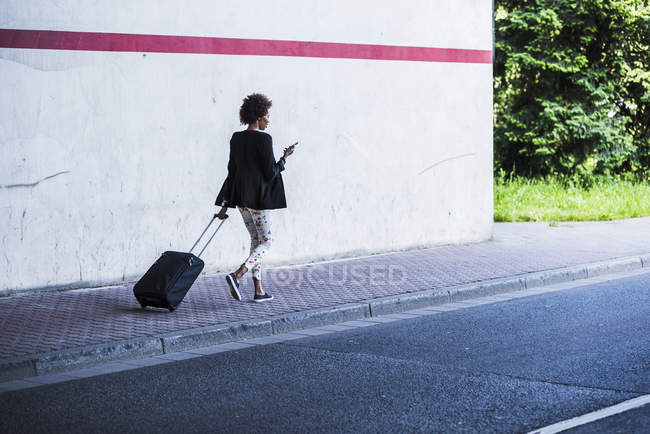 Businesswoman with baggage walking down street — Stock Photo