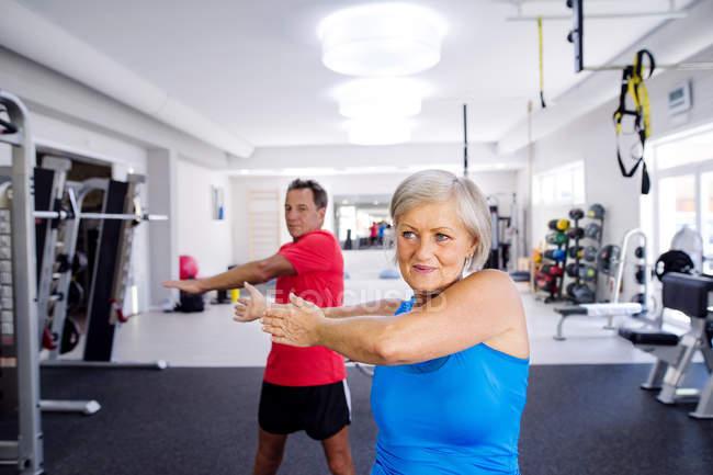 Зрелая женщина и пожилой мужчина занимаются гимнастикой — стоковое фото