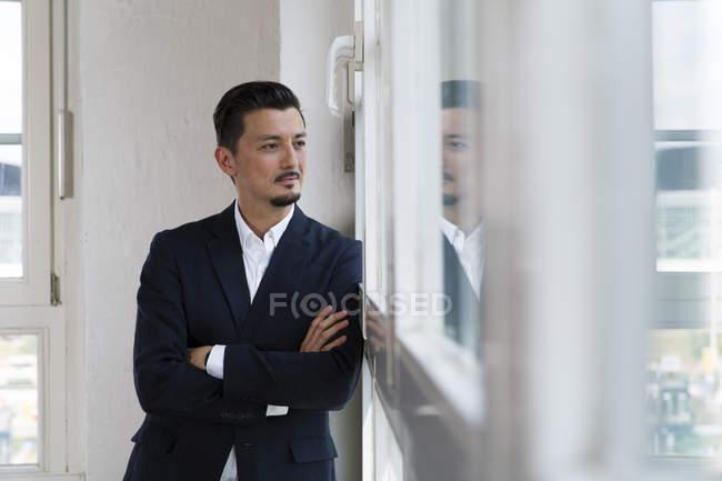 Empresário de pé na janela — Fotografia de Stock