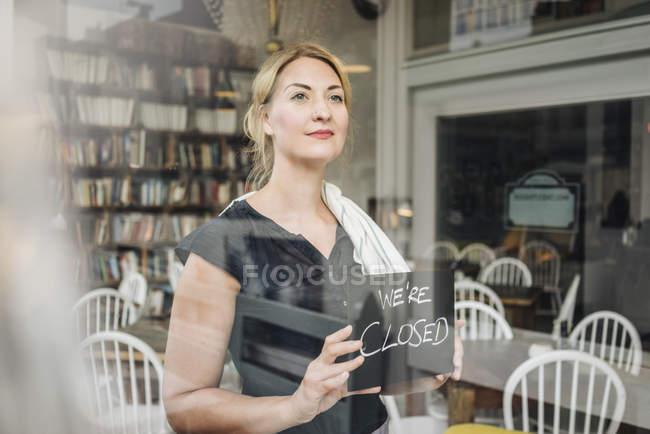 Женщина в кафе с закрытой вывеской — стоковое фото