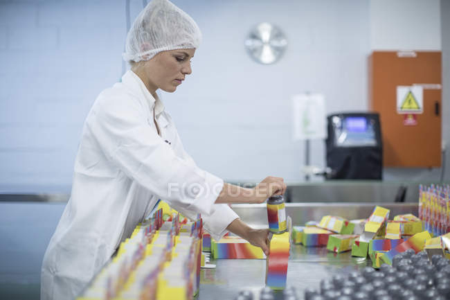 Woman packing flasks in medical factory — Stock Photo
