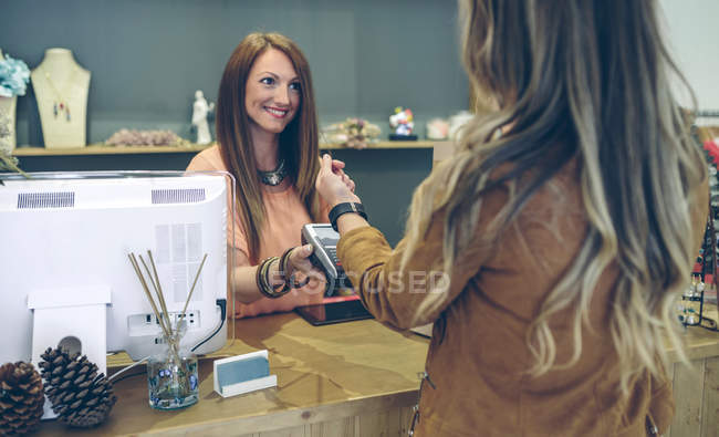 Woman paying using smartwatch with NFC technology in a store — Stock Photo