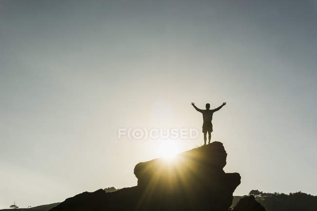 Silhouette of man standing on rock — Stock Photo