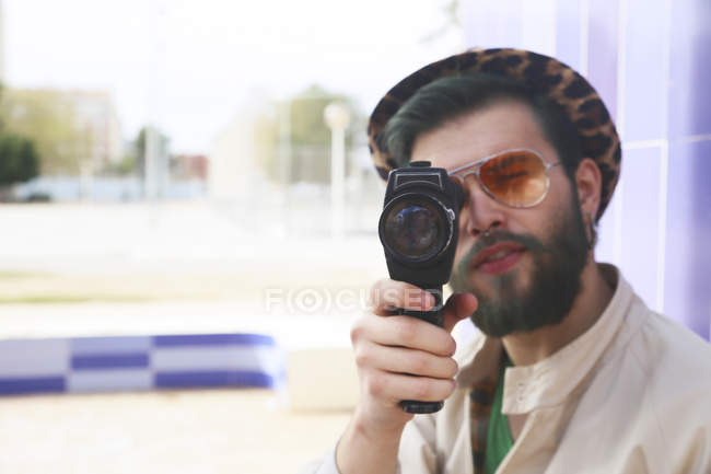 Young man using a vintage video camera — Stock Photo