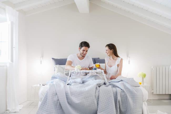 Pareja en la cama con bandeja de desayuno - foto de stock