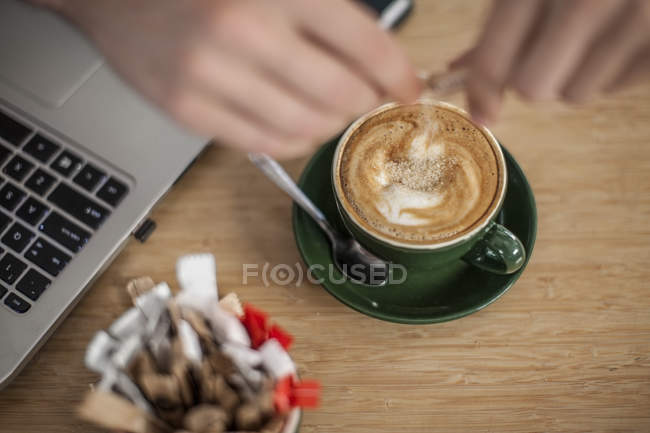 Hand pouring sugar into cup of cappuccino next to laptop — Stock Photo