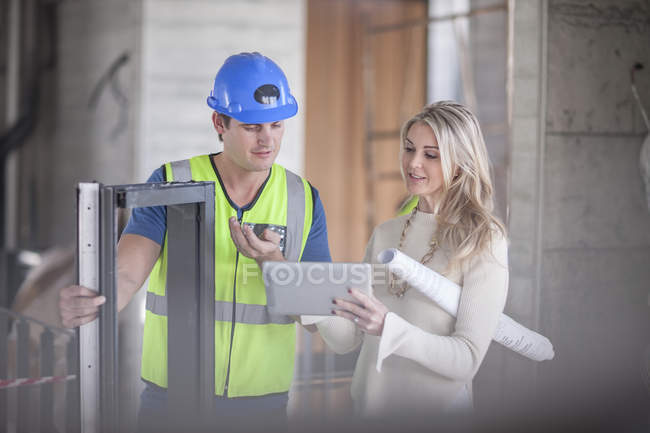 Construction worker talking to woman on construction site — Stock Photo