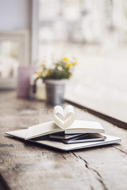 Book on stack of mobile devices — Stock Photo