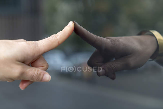Woman's index finger touching glass pane — Stock Photo
