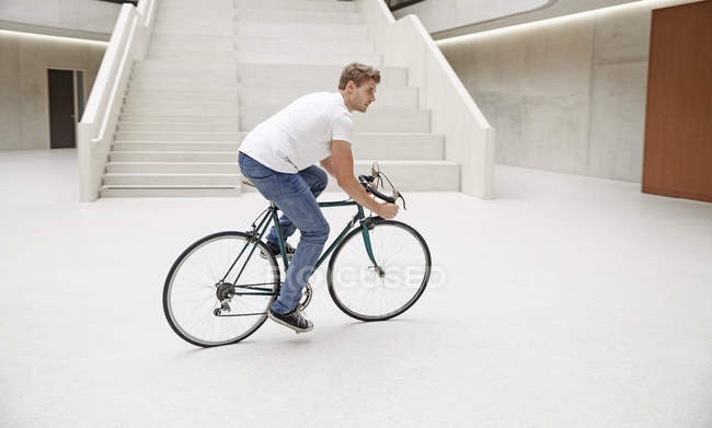 Man riding bicycle in foyer — Stock Photo