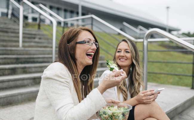 Two laughing women having lunch break outdoors — Stock Photo