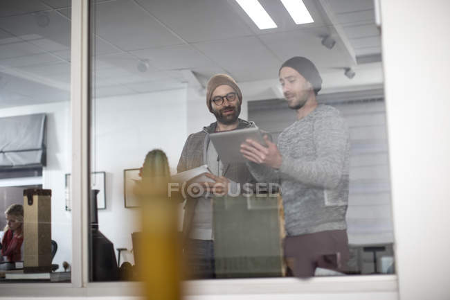 Two creative professionals discussing ideas on digital tablet — Stock Photo