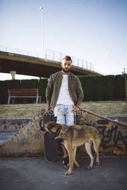 Skateboarder mit Hund steht im Skatepark — Stockfoto