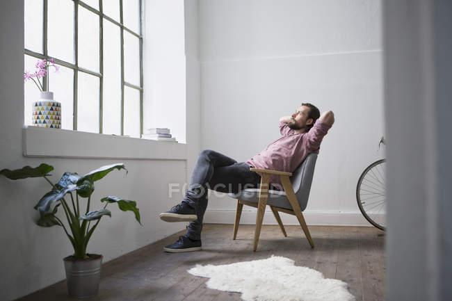 Hombre sentado en la silla y soñar despierto en moderno edificio - foto de stock