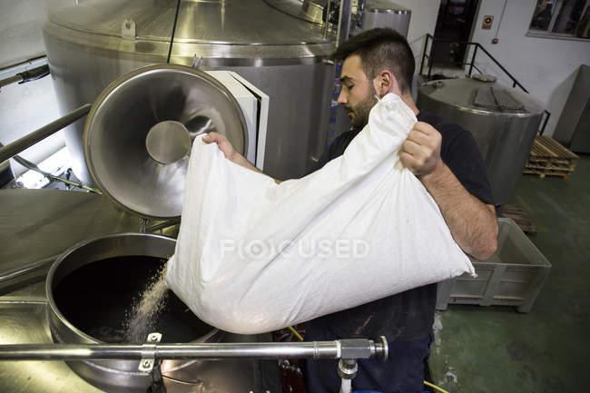 Hombre vertiendo una bolsa de malta en un tanque de cerveza en una fábrica - foto de stock