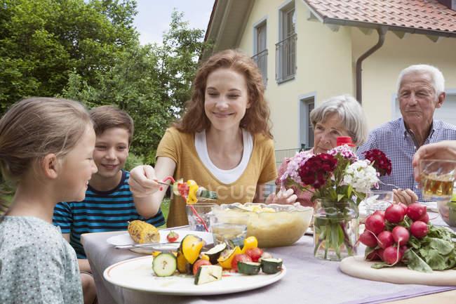 Extended caucasian family dining in garden — Stock Photo