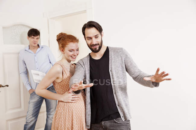 Expecting parents making plans in empty apartment with real estate agent watching — Stock Photo