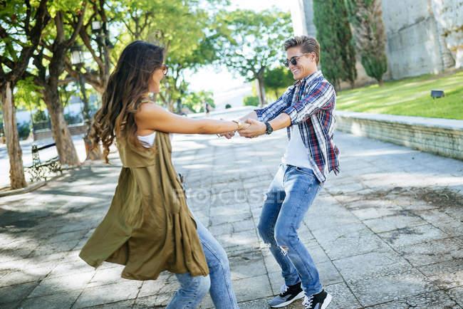 Glückliches junges Paar tanzt zusammen auf dem Bürgersteig — Stockfoto
