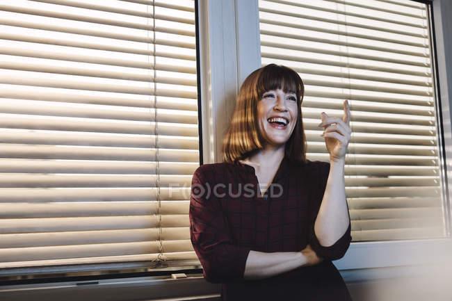 Портрет сміється кавказька жінка біля вікна — стокове фото
